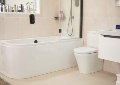 White Bath Shower with matt black taps and matt black shower head shower cord, and matt black bathroom accessories