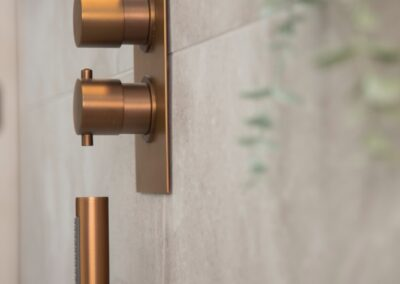 Shower with Bronze taps and shower head, soap dish & Bronze bathroom accessories.