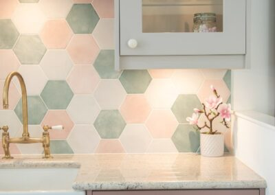 Formosa Showroom Kitchen with green marble counter top, dusky pink and grey cabinets and white handles and hexagonal tiles with pinks and greens.