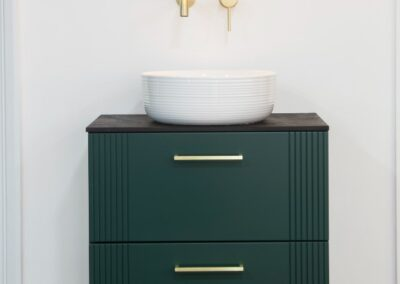 Bathroom unit in dark green gold handles and gold taps