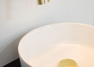 White ceramic circular Bathroom sink bowl with gold push plug and gold taps