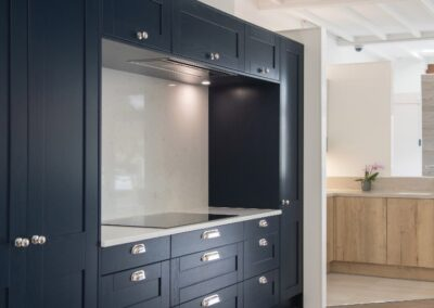 Kitchen with midnight blue and silver theme. Dark Blue Cabinets with silver handles while marble cooker splash back.