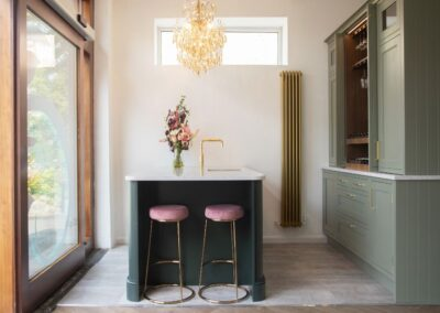 Formosa Showroom Kitchen light green Cabinets gold handles and open wine cabinet, matt gold tall radiator, island with told tap