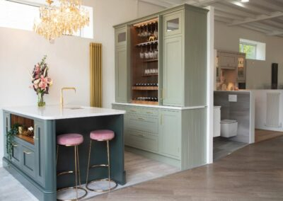 Kitchen with green and gold theme. light green Cabinets gold handles and open wine cabinet, matt gold tall radiator, island with told taps and 'pink velvet stools.