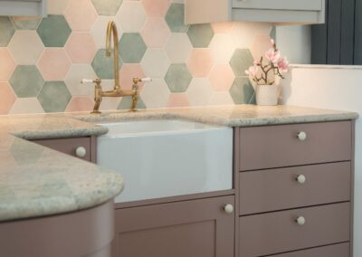 Formosa Showroom Kitchen with green marble counter top, dusky pink cabinets and white handles and hexagonal tiles with pinks and greens.