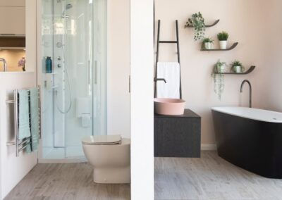 Formosa Showroom shows Two Bathrooms one with shower and one with free standing black bath, shelves and accessories